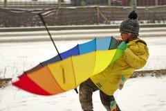 Ombrello di cattura del ragazzino soffiato via da vento Immagini Stock Libere da Diritti