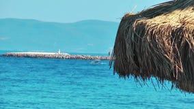 Ombrello di legno vicino alla spiaggia stock footage