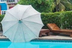 Ombrello di spiaggia con il sedile di legno sul lato dello stagno in hotel fotografia stock