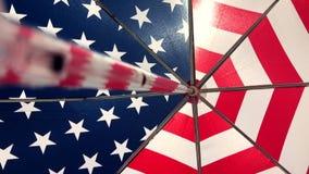 Ombrello di spiaggia della bandiera americana che scuote nel vento archivi video