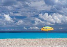 Ombrello di spiaggia e bella spiaggia Myrtos con chiara acqua del turchese un giorno soleggiato nel Mar Ionio sull'isola di Kefal fotografie stock libere da diritti