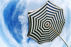 Ombrello di spiaggia a strisce sopra la vista dal basso dell'occhio di pesce del cielo blu Immagine Stock
