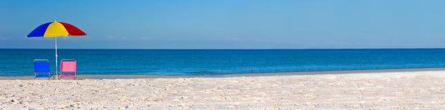Ombrello di spiaggia variopinto di panorama con il rosa e le sedie a sdraio blu fotografia stock libera da diritti