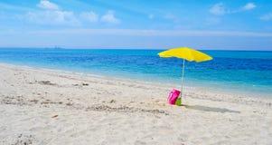 Ombrello e borsa su una spiaggia tropicale fotografia stock libera da diritti