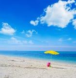 Ombrello e borsa su una spiaggia tropicale fotografie stock libere da diritti