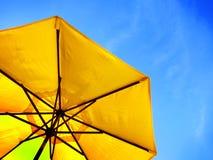 Ombrello e cielo blu gialli Fotografia Stock