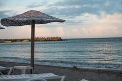 Ombrello e tramonto di Reed sopra la spiaggia Fotografie Stock