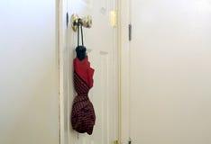 Ombrello rosso che appende sulla manopola di porta Fotografie Stock Libere da Diritti