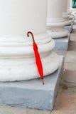 Ombrello rosso vicino all'alta colonna Fotografie Stock