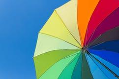 Ombrello variopinto su una priorità bassa del cielo Fotografie Stock