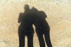 Ombres, contours la silhouette sur le sable ensoleillé en mer peu profonde Photographie stock libre de droits