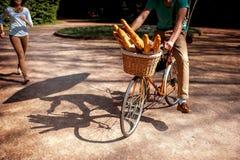 Ombres d'une bicyclette avec le panier plein des baguettes en parc Image stock