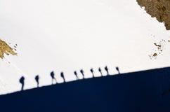 Ombres de groupe de trekkers de montagne sur une neige photos stock