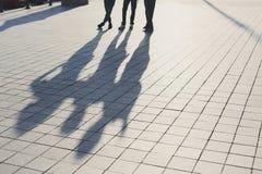 Ombres de trois amis sur le trottoir Photos libres de droits
