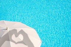 Ombres des mains formant un coeur sur un parasol blanc, fond de l'eau de piscine, concept d'été Images stock