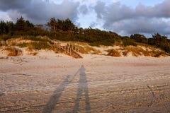 Ombres du père et du fils tenant des mains dans la lumière de coucher du soleil sur t Photos libres de droits