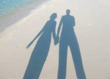 Ombres sur le sable de la femme et de l'homme tenant des mains Photo libre de droits