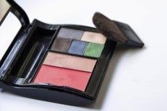 Ombretti e spazzola e cosmetici di trucco, su un fondo bianco isolato, immagini stock