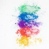 Ombretti luminosi nei colori differenti dell'arcobaleno, sparsi su un fondo bianco immagini stock