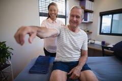 Ombro de exame de sorriso do doutor fêmea do paciente masculino superior Fotografia de Stock Royalty Free