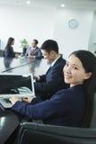 Ombro de Looking Over Her da mulher de negócios na câmera Imagens de Stock
