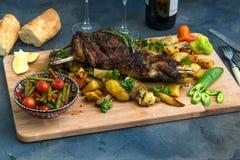Ombro do assado do cordeiro na batata e em cenouras cozidas, placa de madeira, vista superior imagens de stock