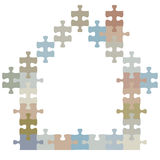 Ome of jigsaw puzzle pieces shape a house. A colorful home as construction of jigsaw puzzle pieces in the shape of a house Stock Images