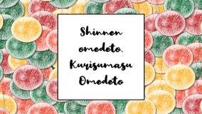 Omedeto de Shinnen La tarjeta de Navidad de Kurisumasu Omedeto con la chuchería de la Navidad como fondo, enfoca adentro almacen de video