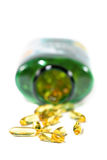 Omega 3. Cod liver oil pills spilling from a bottle Royalty Free Stock Images