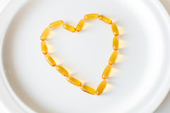 Omega 3 pills in a shape of heart. Omega 3 (fish oil) pills in a shape of heart on a white plate Stock Image