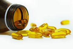 Omega3 capsules. Supplementary food - Omega3 capsules spilled from the bottle Royalty Free Stock Photography
