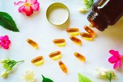 Omega 3 die pillen met gekleurde bloemen op de lijst worden verfraaid royalty-vrije stock foto's
