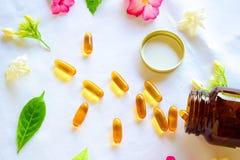 Omega 3 die pillen met gekleurde bloemen op de lijst worden verfraaid royalty-vrije stock afbeeldingen