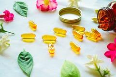Omega 3 die pillen met gekleurde bloemen op de lijst worden verfraaid stock fotografie