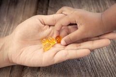 Omega 3 för olja för lever för barnhackatorsk stelnar kapslar på hennes moderhand fotografering för bildbyråer