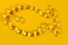 Omega-3 fish fat oil capsules shaped in fish on a yellow. Background Royalty Free Stock Photo