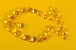 Omega-3 fish fat oil capsules shaped in fish on a yellow. Background Royalty Free Stock Image