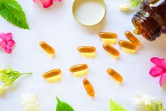 Omega 3 pills decorated with colored flowers on the table stock photography
