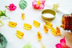 Omega 3 p?ldoras adornadas con las flores coloreadas en la tabla fotos de archivo libres de regalías