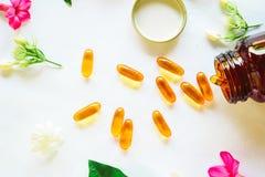 Omega 3 p?ldoras adornadas con las flores coloreadas en la tabla imágenes de archivo libres de regalías
