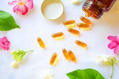 Omega 3 piller som dekoreras med kul?ra blommor p? tabellen royaltyfri fotografi