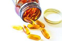 Omega 3 pillole si sparge sulla tavola fotografia stock