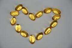 Omega-3 good for heart. Omega-3 pills in shape of a heart stock photo