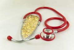 Omega z czerwonym stetoskopem 3 kapsuły Zdjęcia Royalty Free