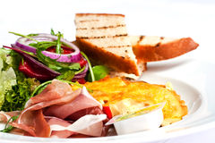 Omelet. With salad, bread and cured ham Stock Photography