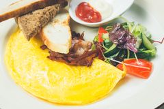 Omelet with bacon served on white plate, vegetables aside Stock Photos