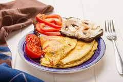 Omelet in a blue plate Stock Images