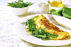 Omelet with cheese and arugula on a white plate. Stock Images