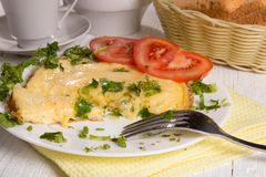 Omelet with cheese and fresh herbs on the table Stock Photo