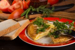 Omelet with cheese and fresh herbs on the table Royalty Free Stock Photo